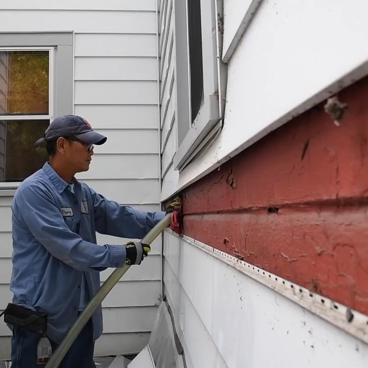 An Energy and Housing service worker stuffing insulation into a house.
