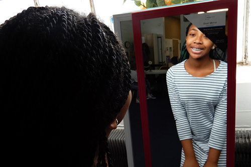 A young girl looks at her reflection at the Eastside Family Resource Center