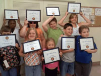 Kids up holding certificates