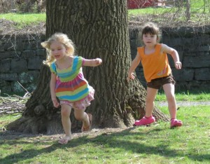 two small girls running on lawn near tree