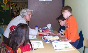 senior woman working with three kids at table