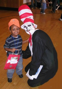 smiling child with adult in Dr. Seuss costume at Halloween