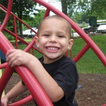 smiling boy with hand on playground equipment