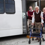 Man helping senior couple outside shuttle bus