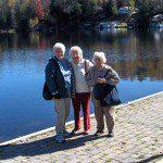 three seniors standing at lakeside